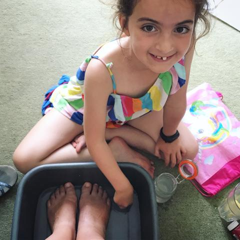 young girl smiles as she tends to her mother's feet