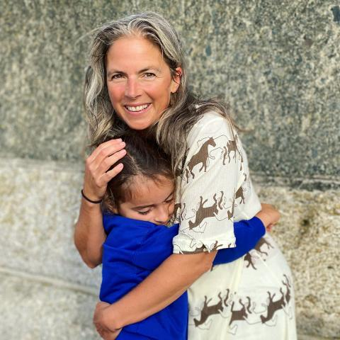 Mother cuddles daughter on the first back to school day. Story of Mum - life coaching for mums.