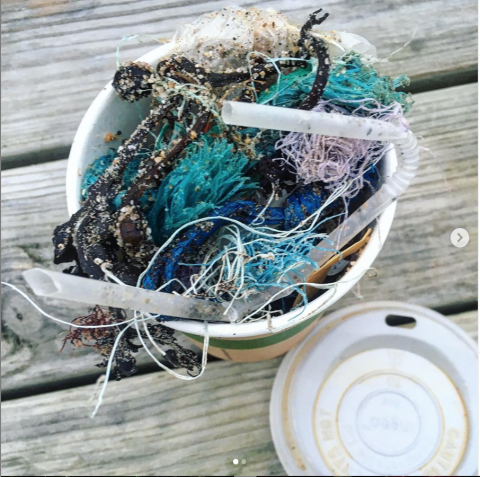 A coffee cup full of beach clean rubbish