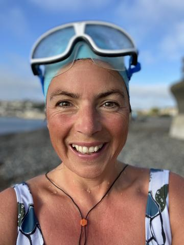 Wearing goggles and a swim hat, Pippa smiles at the camera after a sea swim. Life coaching for mums